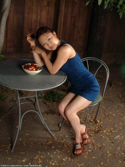 Leggy youthful Oriental gal striptease outdoors to undressed bushy slit