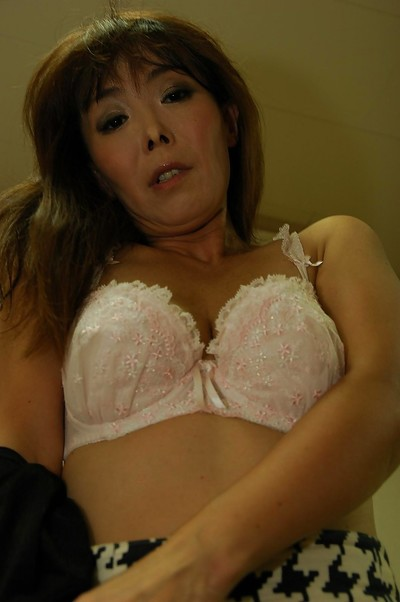Bawdy Japanese MILF Kayo Mukai undressing and posing uncovered on the sofa