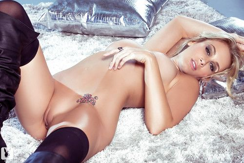 Glamorous blonde in glasses and high-heeled boots uncovering her stunning body