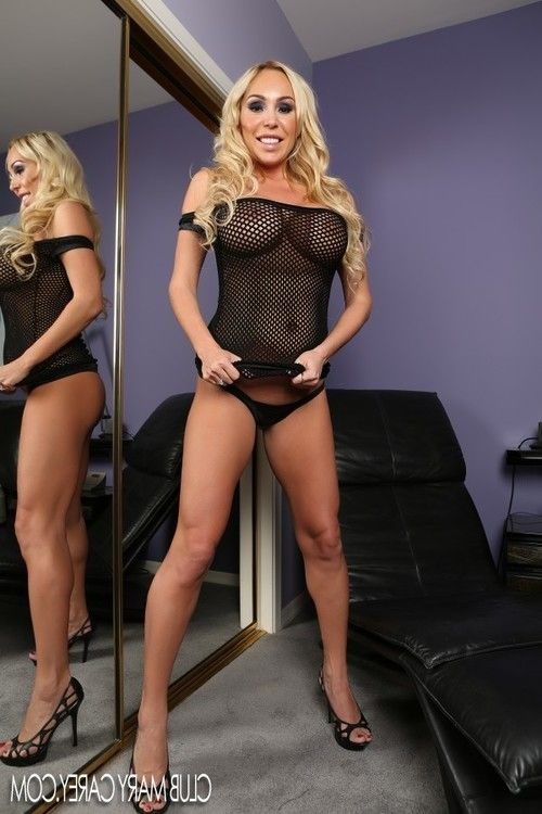 Blond beauty Mary Carey stripped off then fingers her taut little pussy, getting it ready for her large black cock toy.