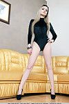 Blond girl Salma C shedding satin onesie and high heels to model undressed