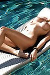 Graceful golden-haired centerfold with round boobies posing at the poolside