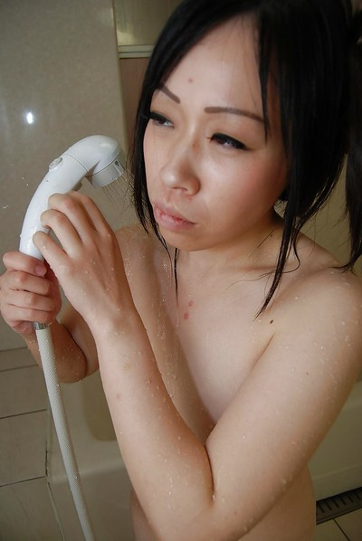 Lusty Japanese juvenile ravishing baths and rubbing her furry cum-hole in close up