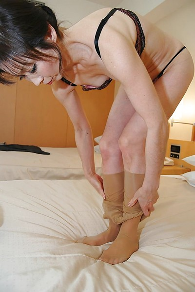 Oriental MILF in hose undressing and exposing her furry bawdy cleft