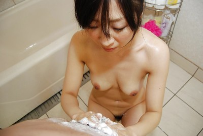 Oriental MILF gives a soapy tugjob and a fleshly nooky in the shower