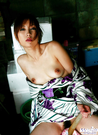 Seductive Japanese cutie showcasing her wonderful bumpers and curly love-cage