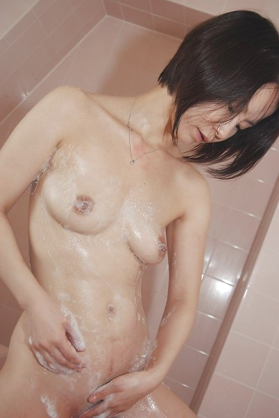 Oriental MILF captivating washroom and teasing her hirsute gash with water jets