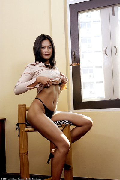 Adolescent Oriental model shedding underclothes and short skirt at the same time as undressing
