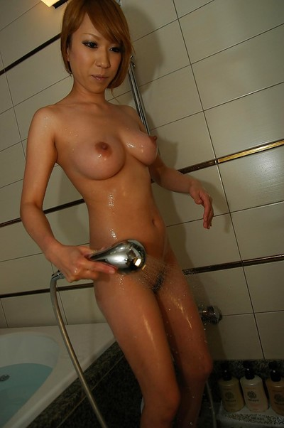 Oriental young Mana Utsumi pleasing baths and exposing her snatch in close up