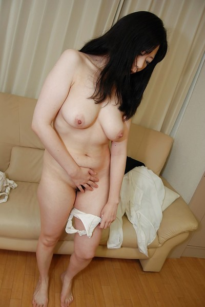 Sassy oriental MILF undressing and exposing her tacky muff in close up