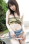 Lusty oriental infant uncovering her mounds and flashing her bush outdoor