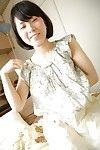Smiley Japanese adolescent striptease down and showing off her trimmed snatch