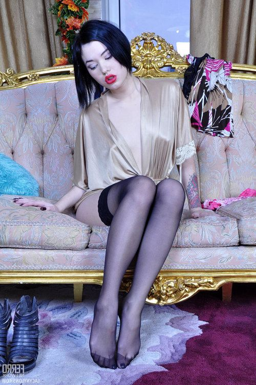 Dark-haired pretty fall in love with the give the impression of her legs in ebon gartered nylons