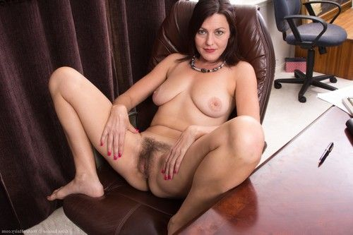 Gina Louise removes clothes by her desk and shows her fur pie