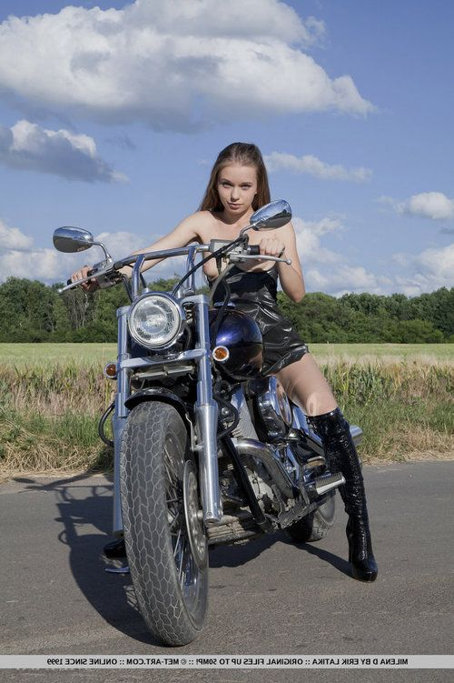Wearing a hot leather suit and boots Milena displays her undersize and nubile body on dominant of a motorcycle