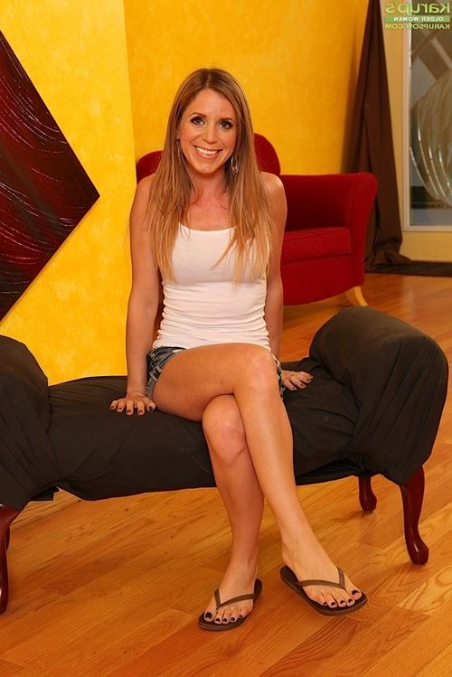 Slender golden-haired mama Carly Bell posing solo in white T-shirt and denim underclothing