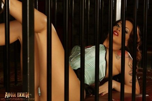 Nikki Nova is locked in a cage wearing a blue corset and panties.