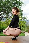 Summer undresses from her brown lace underware outdoors.