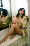 Short haired dark brown can\'t live without self in mirror during sheltered solely in a mink coat.