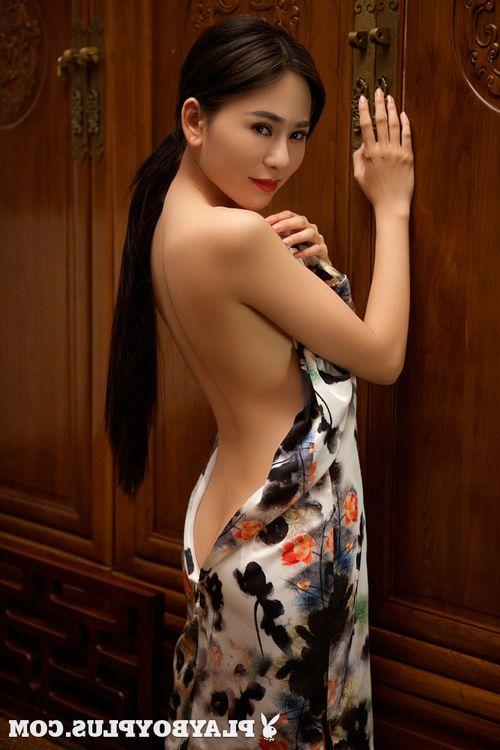 Brunette Asian girl Wu Muxi strips short dress to model nice ass & tits naked
