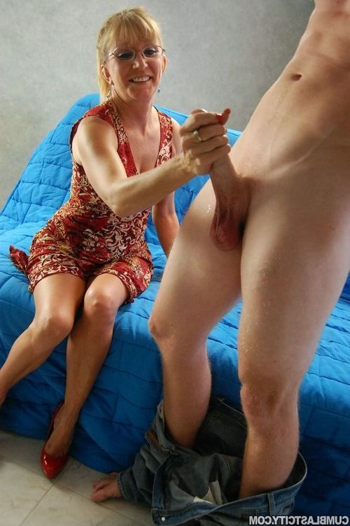 Grown lady in yearn dress gives a handjob and gets bukkaked