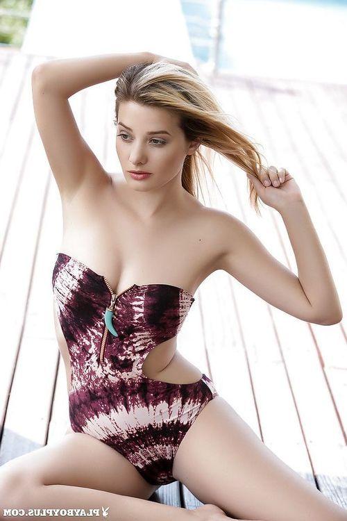 Stunning centerfold model Anna Tatu posing outdoors beside swimming pool