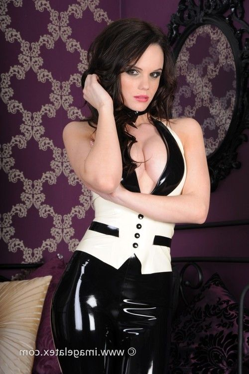 Pretty brunette poses in a tight and shiny latex tuxedo
