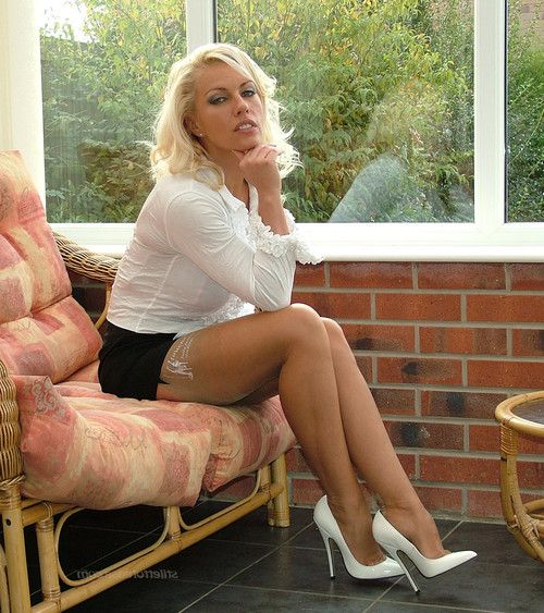 Busty blonde milf showes her nyloned legs in white heels