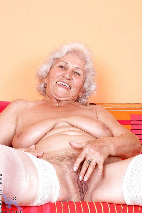 Blond granny in shiny white stockings denudes boobs and masturbates