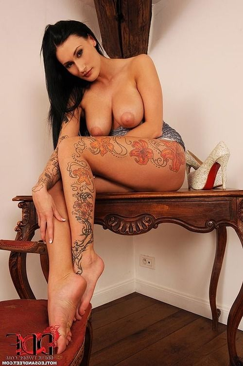 Leggy tattoo model with big natural tits freeing sexy barefeet from heels