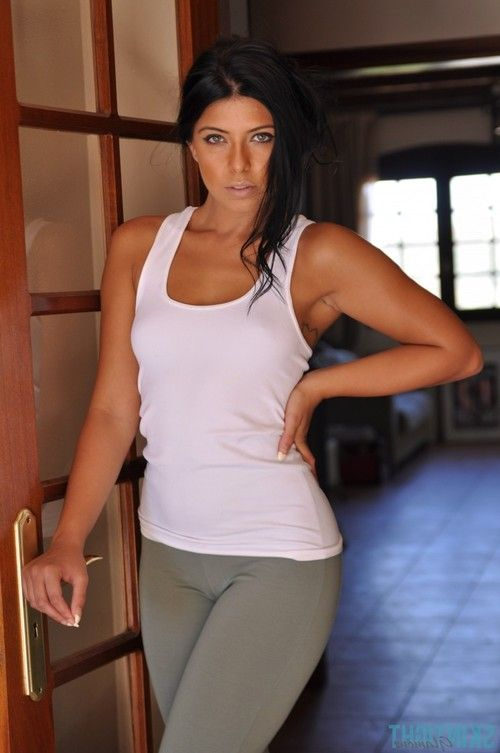 Sporty brunette girl stripping and posing