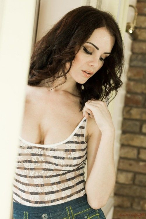 Perfect busty brunette emma glover in front of a window
