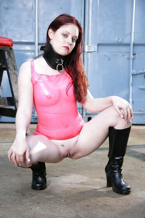 Kinky redhead teen babe in latex top and black boots posing outdoor