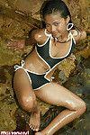 Cute thai brunette strips from her black bikini on the sea shore