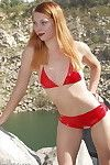 Amateur redhaired exhibitionist poses naked on the rocks beside