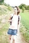 Young Euro girl baring shaved pussy underneath short skirt outdoors in field