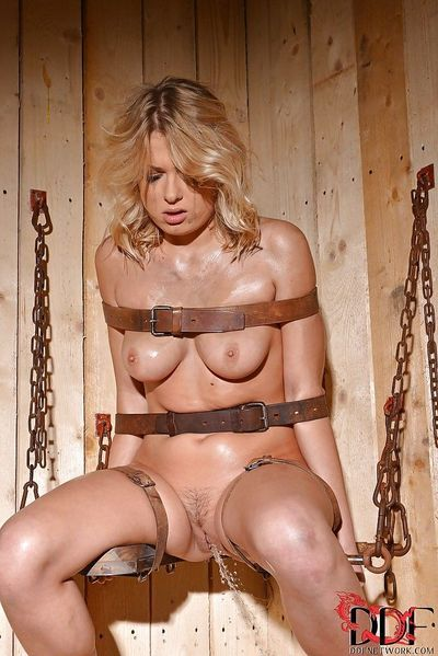 Bound oiled up blonde with trimmed pussy makes some pissing