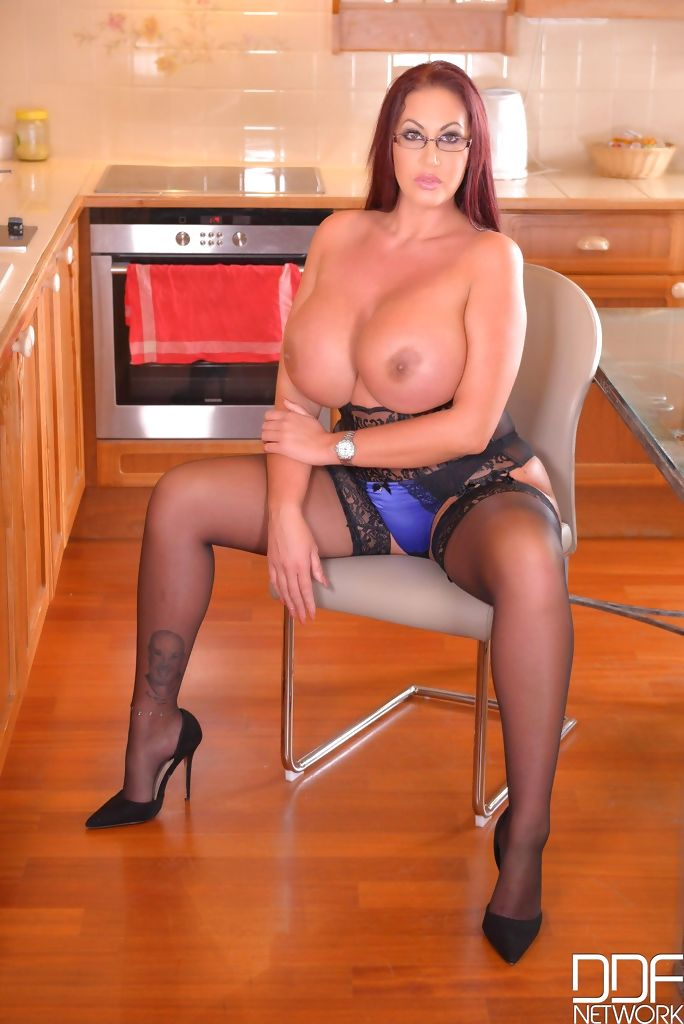 Glasses and stockings wearing MILF Emma Butt flaunts her giant boobs on chair