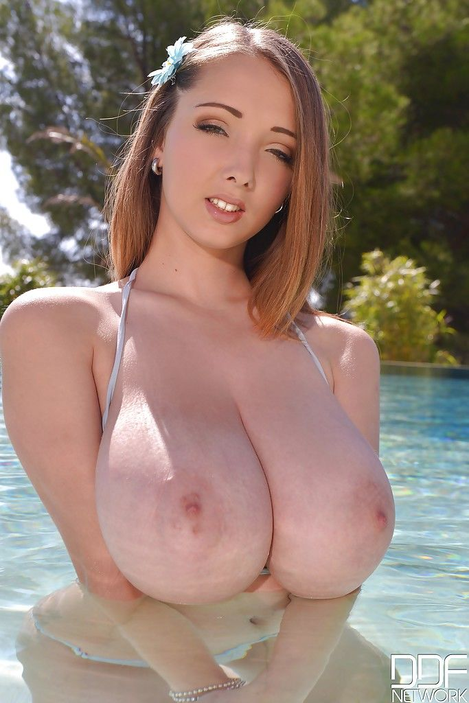 Wet solo girl Lucie Wilde showing off nice melons in swimming pool