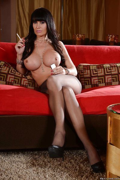 Big busted MILF poses wearing only nylon pantyhose and smoking a cigarette