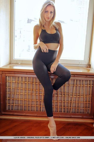 Teen babe slides yoga pants over long legs during glamour shoot