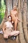 Two sexy lesbian chicks make out and spread their twats in the woods