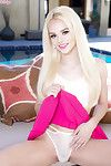 Tiny blonde pornstar Elsa Jean showing off bald pussy beside outdoor pool