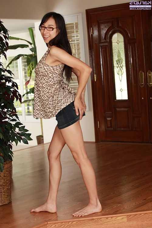 Energetic oriental honey in glasses getting uncovered and fingering her taut gash