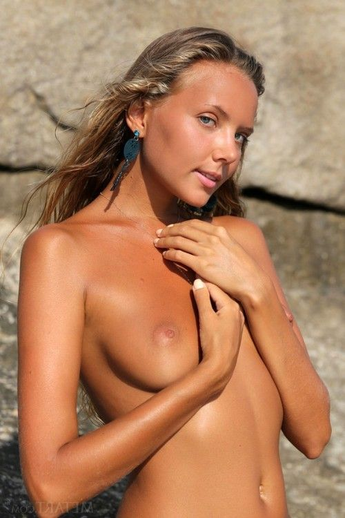 Attractive tanned juvenile lass on some rocks
