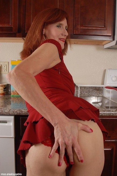Redhead adult Debra is lying as was born on the floor and playing with dick