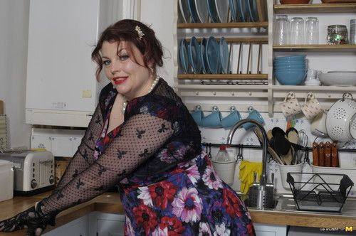 Extra-weighed british housewife playing in her kitchen