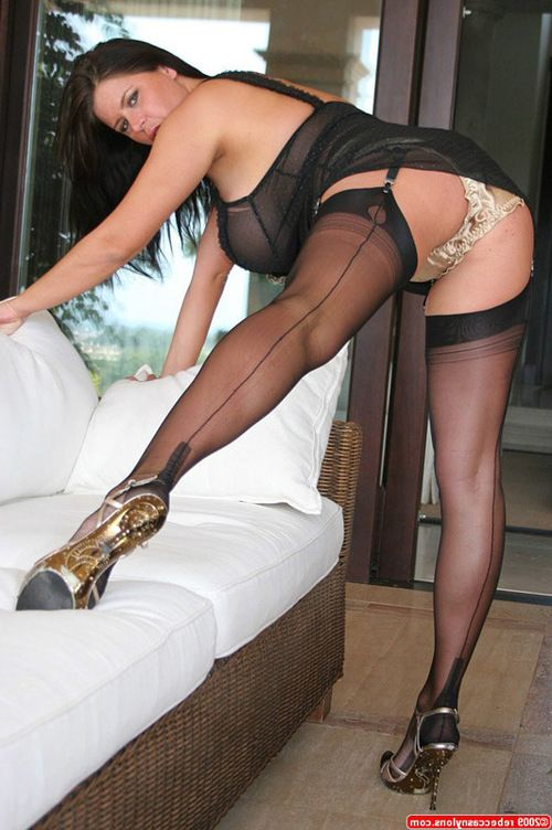 Gigantic breasted brunette hair fatty looks elegant in expensive lingerie, nylons and high heels.