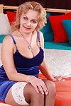 Sexually aroused golden-haired seasoned lady playing on her mattress
